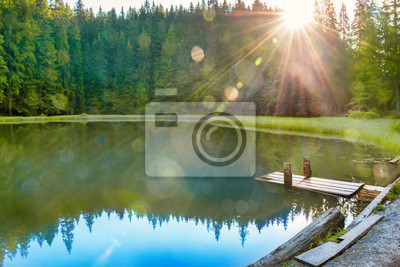 Forest lake in the mountains with blue water, morning light and shining sun