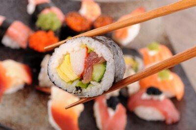 Obraz Futomaki sushi posiadaniu pałeczki