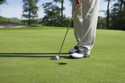 Obraz Golfer taps in with putter on green with trees near a lake