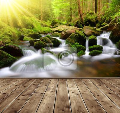 Górski potok z drewnianymi deskami na pierwszym planie. Wiosna las z promieni słonecznych.
