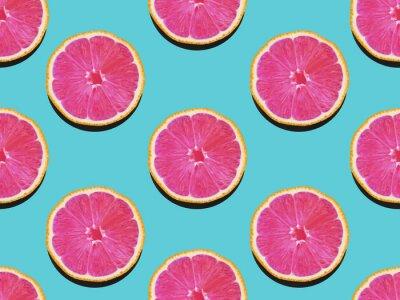 Obraz Grejpfrut w płaskiej świeci Fruity wzór grejpfruta z różowym miąższem na turkusowym tle Widok z góry Nowoczesne mieszkanie lay świeca w stylu pop-art