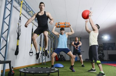 Obraz Group of people in action doing crossfit exercises