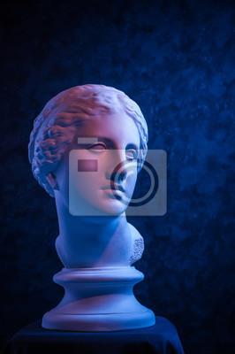 Obraz Gypsum copy of ancient statue Venus head on a dark blue textured background. Plaster sculpture woman face.