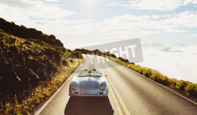 Obraz Happy Couple Driving on Country Road in Classic Vintage Sports Car