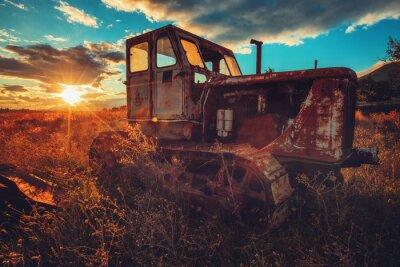 Obraz HDR wizerunek stary ośniedziały ciągnik w polu. Zachód słońca strzał