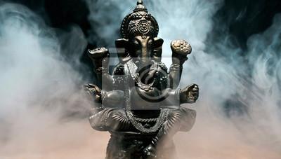 Obraz Hindu god Ganesha on black background. Statue with a smoke of incense.