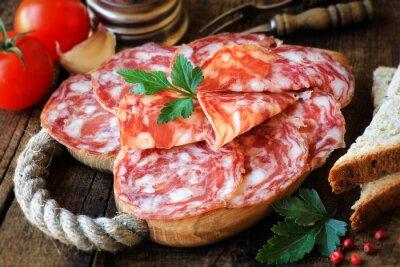 Obraz Hiszpańskie tapas - plastry salame na tamtejsze drewnianą deskę do krojenia chleba i pomidorów