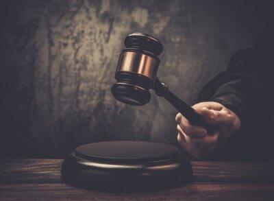 Obraz Hold młotek sędziowski na drewnianym stole