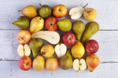 Obraz jabłka i gruszki całe i halved strzał z góry na białych desek