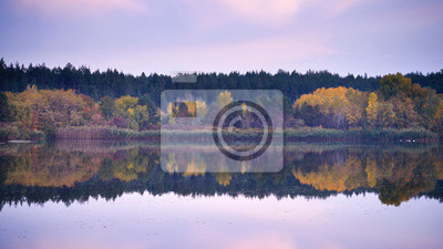 jezioro z powierzchnią lustra w jesienny wieczór i różowe chmury