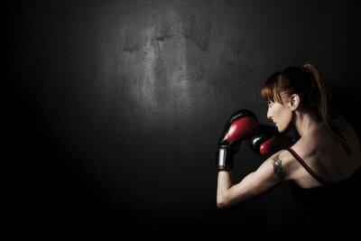 Obraz Kobieta bokser z czerwonym rękawice na czarnym tle, wysoki kontrast z filtrem uwypuklają w studio grunge