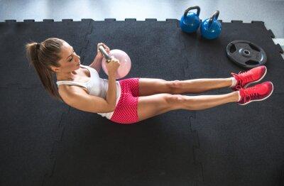 Obraz Kobieta pracująca na jej brzucha z Kettlebell