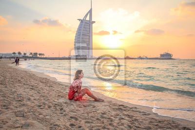 Obraz Kobieta siedzi na plaży o zachodzie słońca 1