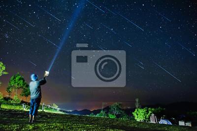 Obraz kobieta świeci oświetlenie gwiaździstym nocnym niebem z deszczem meteorów