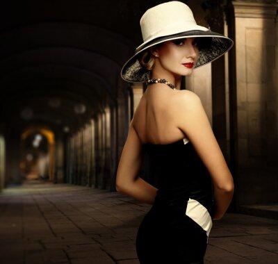 Obraz Kobieta w czarnej sukni i wielkim kapeluszu białym sam, na zewnątrz, w nocy