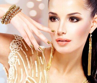 Obraz Kobieta ze złotymi paznokciami i piękna biżuteria złota