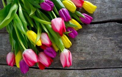 Obraz kolorowe tulipany na powierzchni drewnianych