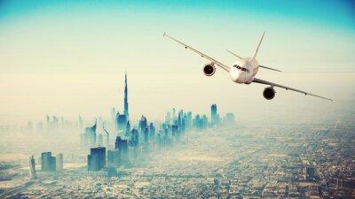 Obraz Komercyjne samolot latający nad nowoczesnym mieście