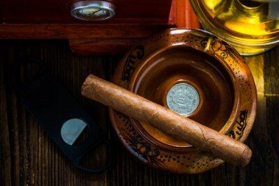 Obraz Kubańskie cygaro w popielniczce z kieliszkiem koniaku reklam humidor