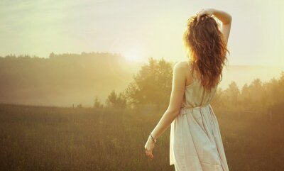 Obraz Ładna brunetka kobieta oglądania zachodu słońca