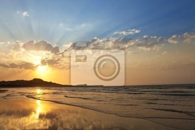 Ładny zachód słońca z dużą ilością promieni słonecznych na plaży samotna