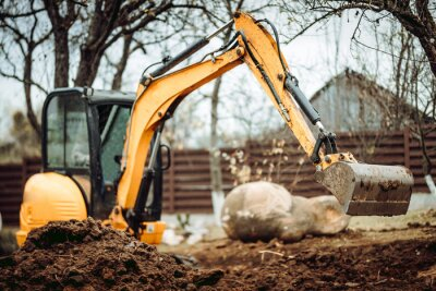 Obraz Landscaping works with mini excavator at home construction site. Terrain works
