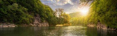 Obraz las rzeka z kamieni na wybrzeżu na zachód słońca