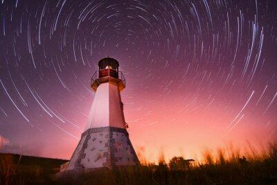 Obraz Latarnia morska z nocnego nieba na tle gwiazdkowych szlaków