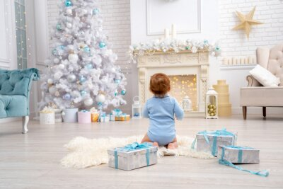 Obraz little baby sitting on a rug with gift boxes in Christmas decorated living room