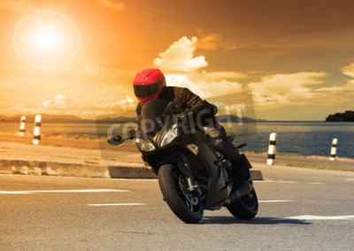 Obraz M? Ody cz? Owiek jazda du? Y motocykl roweru przed ostry krzywej asfaltu wysokie sposoby drogowego z obszarów wiejskich sceny jeziora sceny wykorzystania dla m ?? czyzn przygody i hobby hobby sportowe