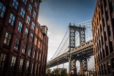 Obraz Manhattan Bridge widziany z wąskiej alejki otoczone dwóch budynków murowanych w słoneczny dzień w lecie