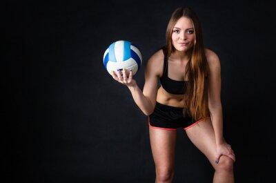 Obraz Młoda dziewczyna trzyma w siatkówkę na czarnym tle