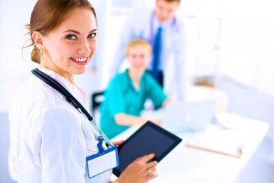 Obraz Młoda kobieta lekarz trzyma tablet PC