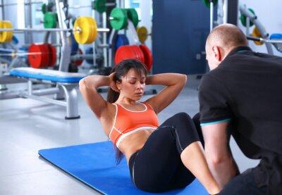 Obraz Młoda kobieta z jej trener na siłowni