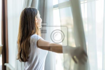 Obraz Młoda ładna dziewczyna otwiera zasłony w sypialni