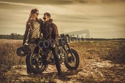 Obraz Młoda, stylowa cafe racer para na vintage motocykle na zamówienie w polu.