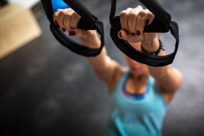 Obraz Młode samice na siłowni pracuje na jej brzucha na TRX