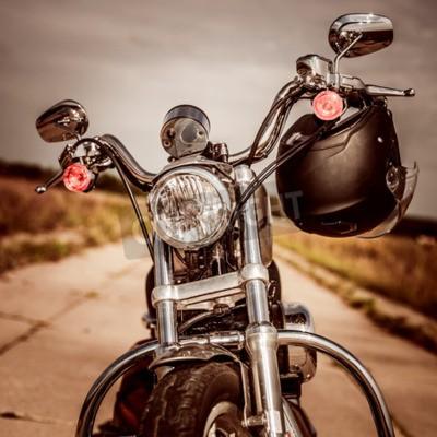 Obraz Motocykl na drodze z kaskiem na kierownicy.