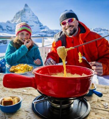 Obraz Narciarze w restauracji, Fondue, tradycyjne szwajcarskie danie - Matterhorn w Alpach szwajcarskich w tle