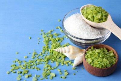 Obraz pachnące zielony i biały sól morska jest w szklanej miski i drewniane bowl.Scattered wokół zielonej soli morskiej z muszli na niebieskim drewnianym stole z muszli