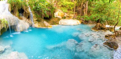 Panorama of emerald blue lake with rock cascades of stream waterfall in tropical jungle forest. Landscape of Erawan National park, Thailand