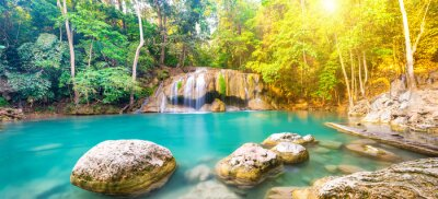 Panorama of tropical waterfall landscape with beautiful wild rainforest with green foliage and flowing water. Erawan National park, Thailand