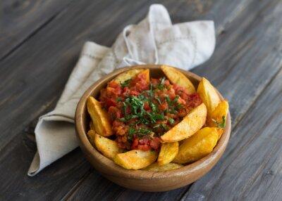 Obraz Patatas bravas, tradycyjne hiszpańskie tapas, pieczone ziemniaki z pikantnym sosem pomidorowym w drewnianej misce na drewnianym stole. Selektywna fokus