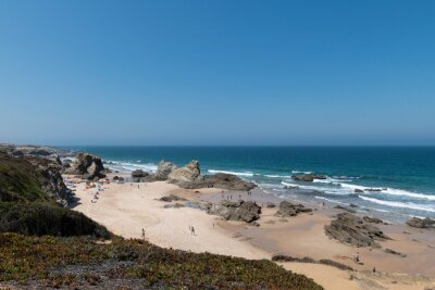 People at the beach during the summer in Porto Covo, in Alentejo, Portugal.