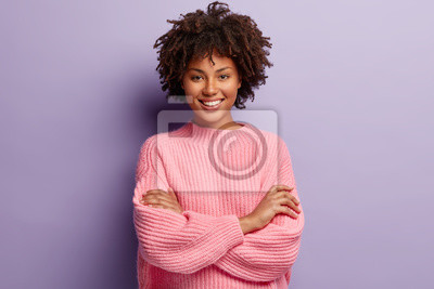 Obraz Photo of self confident pleased dark skinned woman keeps arms folded, smiles gladfully while watches funny programme, has natural appealing beauty, wears oversized pink jumper, poses indoor.
