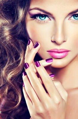 Obraz piękny model z kręconymi włosami i manicure fioletowym