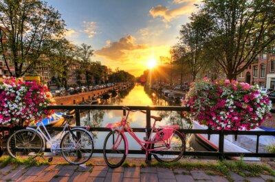 Obraz Piękny wschód słońca nad Amsterdam, Holandia, z kwiatami i rowerów na moście na wiosnę