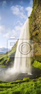 pionowe panoramy z wodospadem i zielona trawa w Islandii