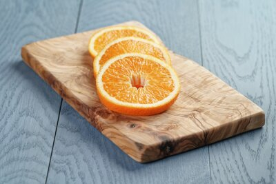 Obraz plastry dojrzałych pomarańczy na deskę do krojenia z oliwek, płytkie fokus