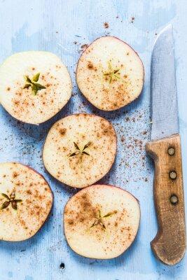 Obraz Plastry świeżych organicznych jabłek z cynamonem na stole